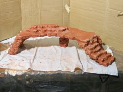 This site has instructions and videos on how to create your own Fake Rock Walls, Bridges, Waterfalls and More for your pet's habitat. Projects range from beginner to expert level :) PICTURED HERE: beginner level bridge / platform project.