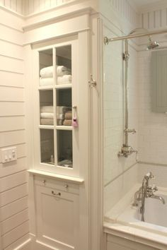 built-in bathroom storage cabinets flanking a tub - Google Search