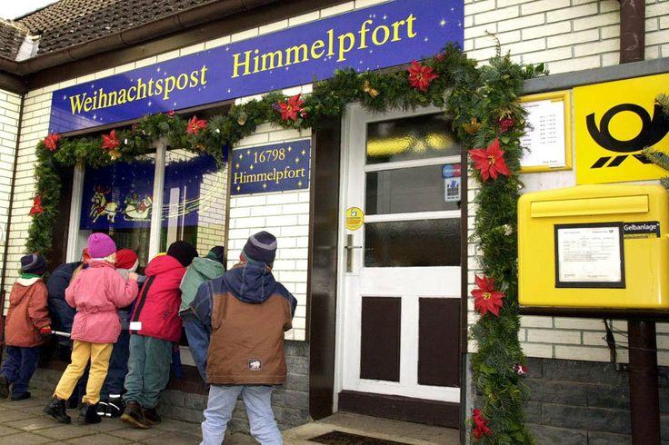 in Himmelpfort (Brandenburg) im Weihnachtspostamt einen Brief mit Wünschen an den Weihnachtsmann einwerfen