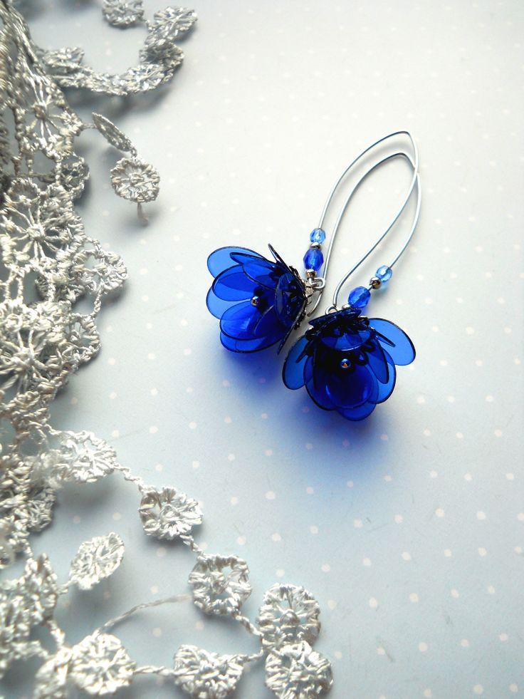 ...kapky Náušnice zdobí poupata z modrých plastických hmot, doplněná jsou skleněnými korálky a kovovými kaplíky. Poupátka jsou zavěšena na atypickém ocelovém náušnicovém háčku, který je ještě dozdobený perličkami.