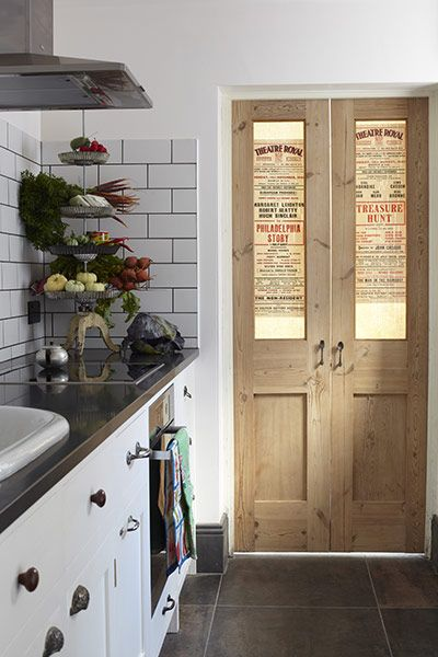 The cupboards on this Shaker-style kitchen were made by Sussex cabinetmaker, Levick Jorgensen, with mismatched vintage knobs and handles. For a similar kitchen off-the-peg try Davonport. The sink, now re-enameled, was originally a cast-iron baby bath, reclaimed from a Netherlands orphanage . The splash-back has an industrial feel with metro tiles and grey grout. The utility room door has been decorated with Brighton theatre billheads.