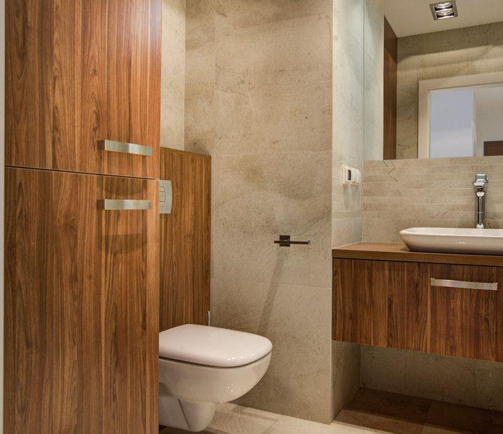 Drewniane elementy w aranżacji łazienki. Drewniana szafka pod umywalką, drewniana obudowa toalety oraz drewniane meble łazienkowe. Reszta łazienki utrzymana w stonowanej, beżowej kolorystyce.