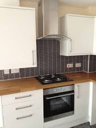 white gloss kitchen units with wooden worktop and grey tiles-- this is very similar to our new kitchen!
