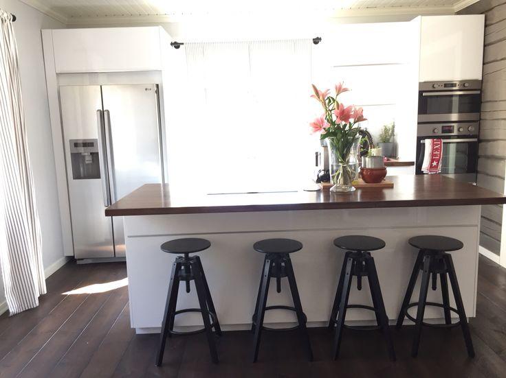 Valkoinen keittiö, tumma lattia, käsitelty hirsi, paneelikatto, massiivipuutasot