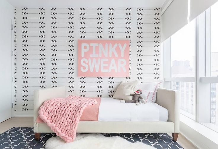 """Tan and pink toddler's room features an accent wall clad in black and white arrows wallpaper lined with a """"pinky Swear"""" canvas art placed over a tan upholstered twin bed dressed in white and pink hotel bedding as well as a pink knitted blanket atop a navy rug by Madeline Weinrib."""