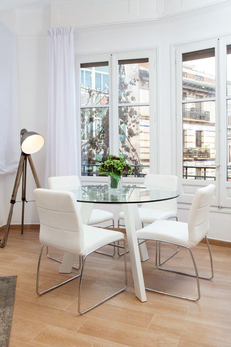 Idea para decoración de sala de estar con gran ventanal mirador: Mesa redonda de cristal y sillas blancas. Original detalle de lámpara de pie trípode inspirada en el cine