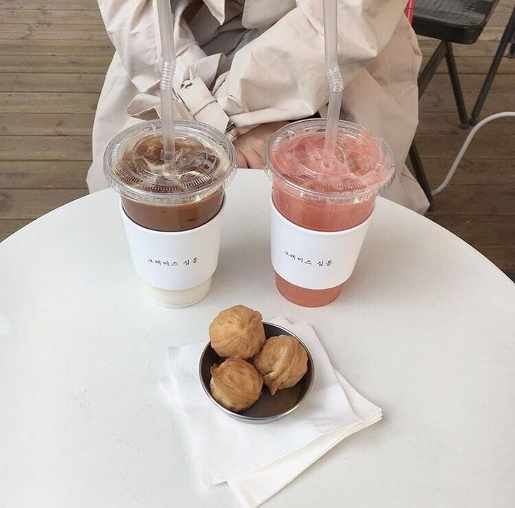 two iced drinks in plastic cups, pink and brown behind clear lids. three pastries piled in a pyramid between on a paper napkin. coated person sitting at a round table.