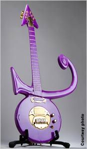Purple guitar with arrow-shaped neck, mounted on stand (Photo by Erin de Jauregui)