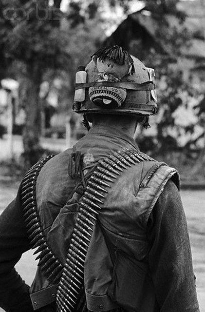 """Feb 1968, Hue, South Vietnam --- A Souvenir doll with the slogan """"Cheer Up"""" adorns the helmet of this fighting U.S. Marine in Hue. --- Image by © Bettmann/CORBIS"""