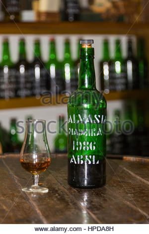 Bottle of madeira wine and wineglass on the winebarrel in Funchal, Madeira - Stock Image