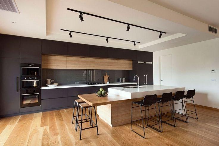 cuisine linéaire en noir mat avec îlot central fonctionnel et chaises de bar noires