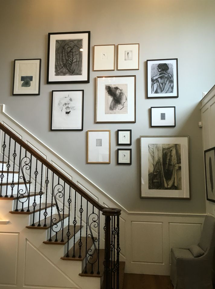 Here's a wonderful stairwell grouping - the deep hues and metallic frame finishes work so well with the wood and iron in the space. The neutral matting pulls all of the pieces together. Stunning!