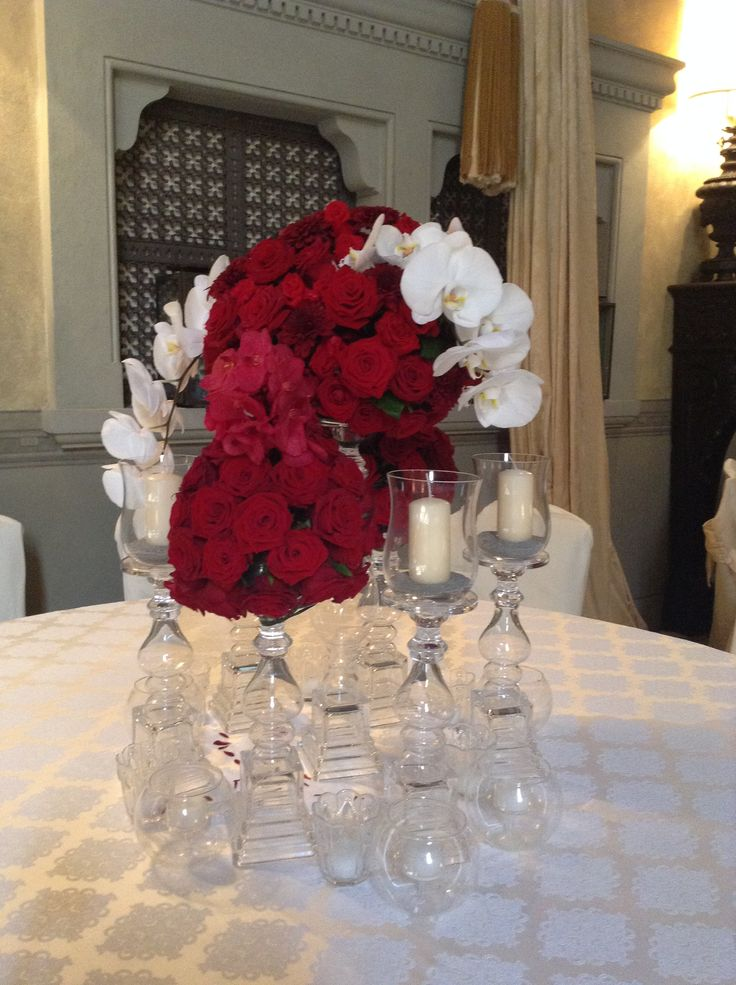 Red roses and orchids centerpiece with candle holders