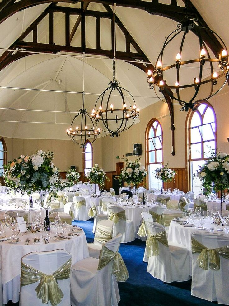 Wedding of Michele and Lyndsay - extravagant tall floral centrepieces of peach and cream The Flower Barrow) tower over crisp white linen and silver Mercury glass tea lights, chair covers accented with antique gold sashes (A Touch of Elegance) - Mission Estate Winery, HAWKES Bay