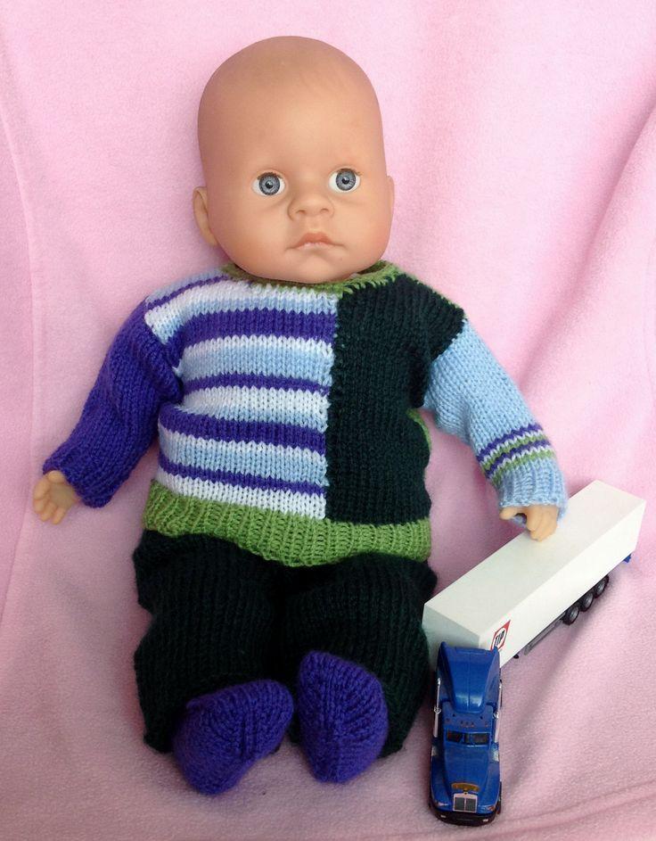 gebreid: veelkleurige trui met effen groene achterkant (idem als boord); donkergroene broek en paarse sokjes