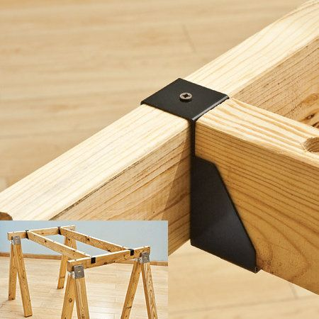 Saw Horse Supports [Rockler] - brackets that slip over the saw horses and hold another 2×4 or two for supporting the middle of the table.  A four-pack of steel brackets runs around $13.