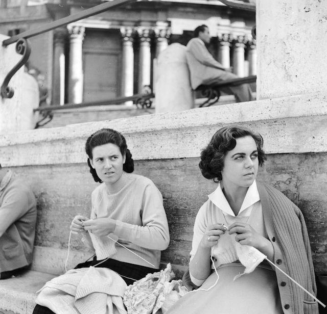 Due ragazze lavorano a maglia vicino alla fontana di Trevi a Roma, mentre tengono d'occhio i turisti lì attorno, nel 1955.