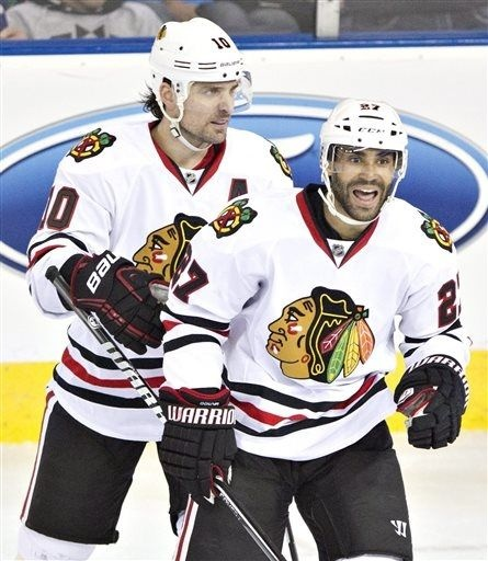 Chicago Blackhawks Johnny Oduya, 27, and Patrick Sharp celebrate a goal against the Edmonton Oilers during third period NHL hockey action in Edmonton, Alberta, Wednesday, April 24, 2013. (AP Photo/The Canadian Press, Jason Franson)