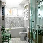 bathrooms - green accent chair gray yellow white Saltillo tiles white caesarstone countertop white wood vanity baskets ornate frameless mirror white beadboard frameless glass shower white cupboard bathroom