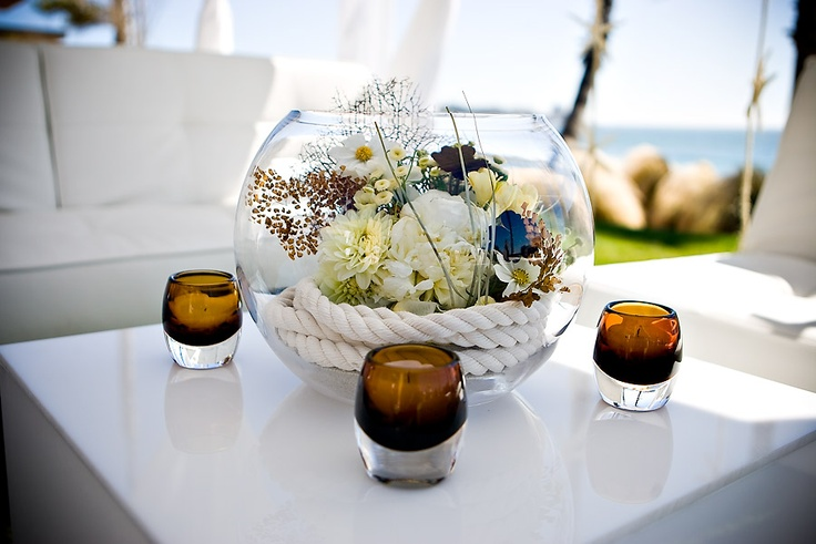 Rope inside a glass bowl with flowers and tea lights around it.  Could be cute with sea shells as well.