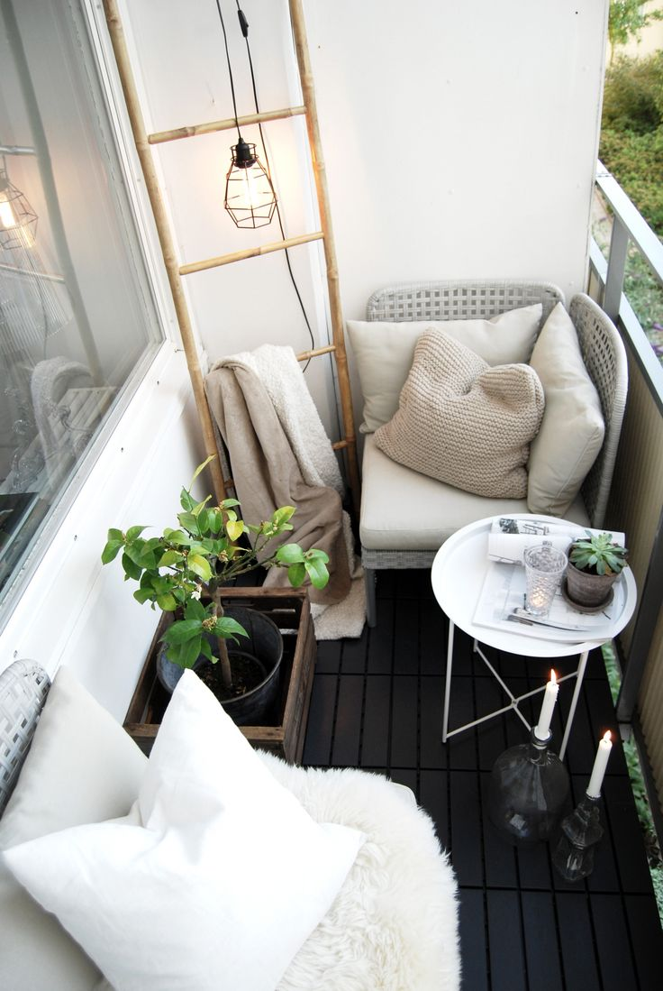 cozy living room space / balcony complete with plants, exposed industrial hanging light and wooden ladder.