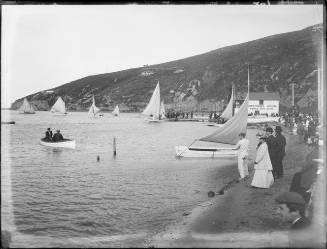 Christchurch Sailing and Power Boat Club, with sloop type sail boats racing and unidentified spectators lining the beach front, steep hillside with a few houses beyond, Redcliffs, Christchurch
