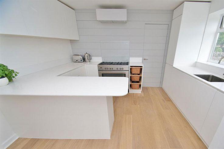 Minimalist white kitchen with concealed door and Corian worktops