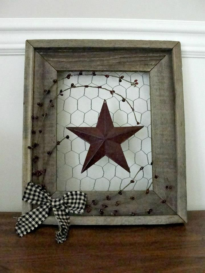 """15 - Barnwood framed burgundy barn star on chicken wire with burgundy pip berries and black gingham bow. Measures 14 3/8""""H x 12 1/4""""W"""