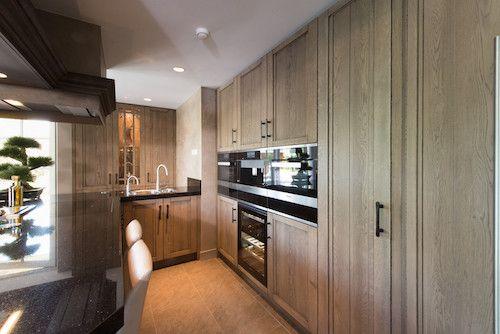 Een koloniale, landelijke keuken met een kookeiland en hoge houten kastenwand. Keukendealer: www.tielemankeukens.nl