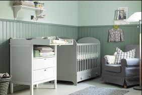 A nursery with Children's IKEA changing table, crib, armchair, rug and floor lamp.