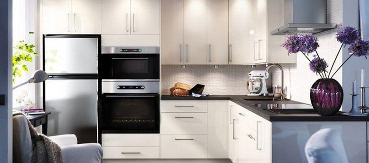 cuisine blanche et moderne avec plan de travail noir et appareils électroménagers encastrés