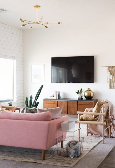 Loving this bright, airy living room space featuring white walls and high ceilings. Layered rugs / pink sofa / west elm light fixture