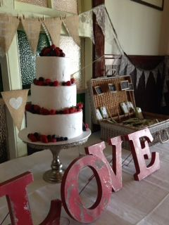 Rustic white buttercream cake with fresh berries on vintage silver stand