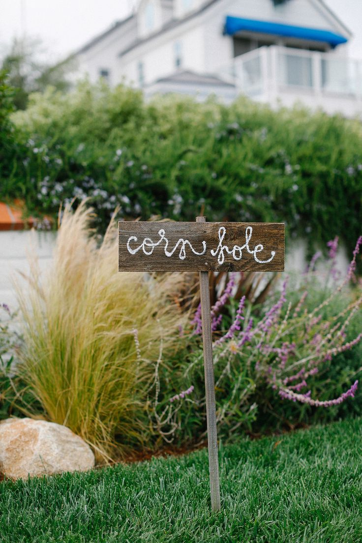 Rustic Cornhole Game Sign | Photography: Luke & Katherine Griffin for Max & Friends. Read More: http://www.insideweddings.com/weddings/tent-wedding-with-chic-nautical-theme-on-la-playa-bay-in-san-diego/737/