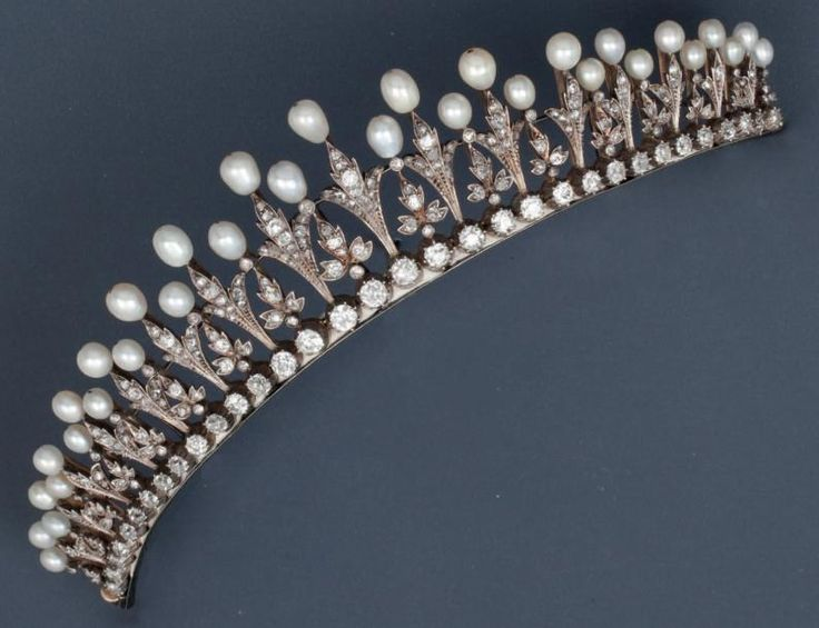 A diamond and baroque pearl tiara, with fleur de lys motifs and floral spacers.