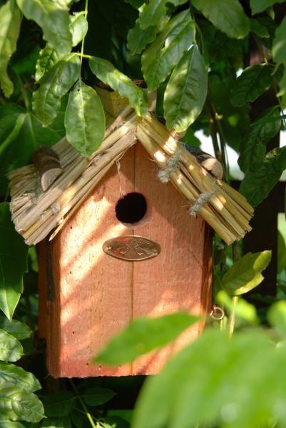 Fából készült madárház szalmatetővel.