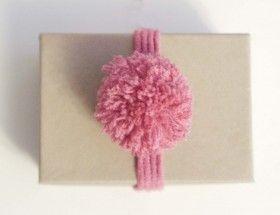 Lag et pent bånd og en pompong av restegarn, og bruk som dekor på en gavepakker.