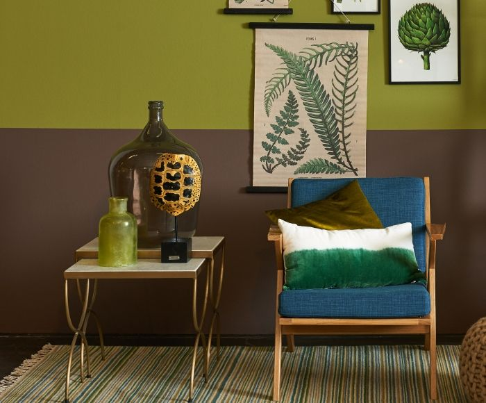Een lambrisering schilderen in de kleuren lever en licht olijf groen, geeft dit  interieur een stoere basis. De botanische prenten en groene accessoires verraden dat  hier een natuurliefhebber huist.