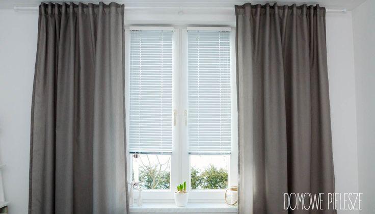 Białe matowe żaluzje aluminiowe 25mm i szare zasłony w sypialni.