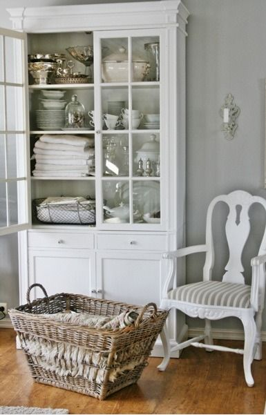 White cupboard, cabinet and white chair with gray walls.