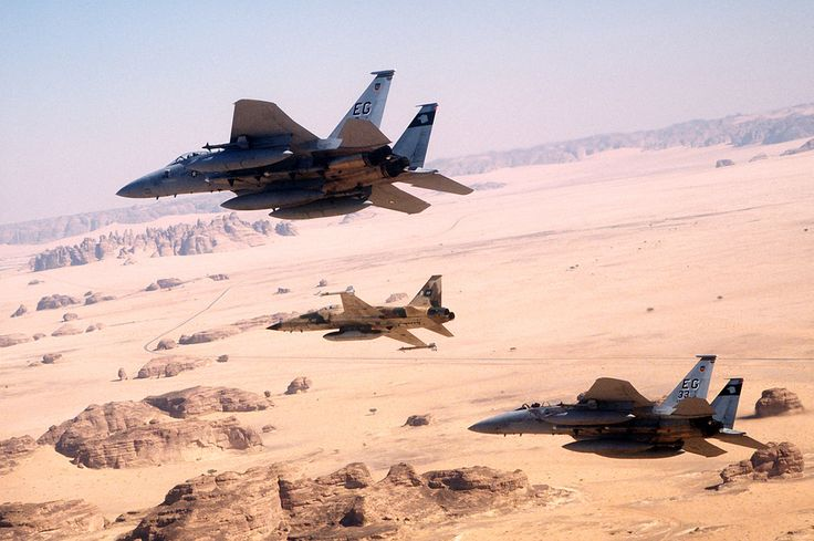 An air-to-air view of two U.S. Air Force F-15C Eagle fighter aircraft from the 33rd Tactical Fighter Wing, Eglin Air Force Base, Fla., and a Royal Saudi Air Force F-5E Tiger II fighter aircraft during a mission in support of Operation Desert Storm. The aircraft are armed with AIM-9 Sidewinder air-to-air missiles.