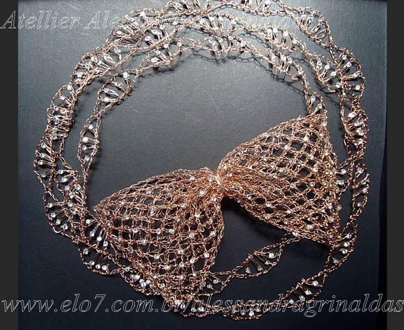 Tiara em rendinha de fio de metal finissimo, com aplicações de strass. Laço com tiara de duas voltas. R$344,90