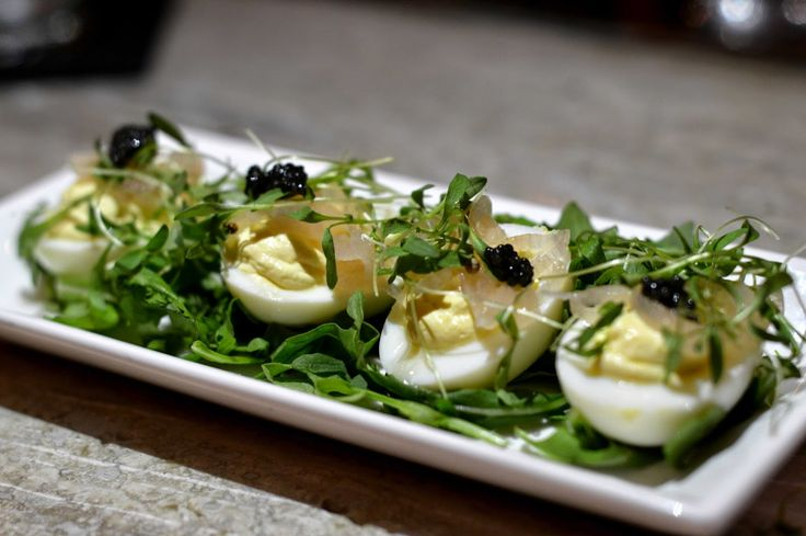 Deviled eggs topped with caviar at The London Bar, NYC. The London Bar is part of the Maze Restaurant by Gordon Ramsay