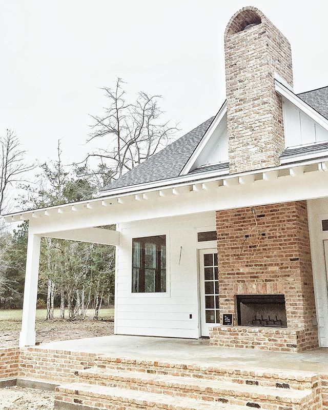 Outdoor fireplace - white farmhouse - black windows - exposed rafters on porch (not sure what it's called)