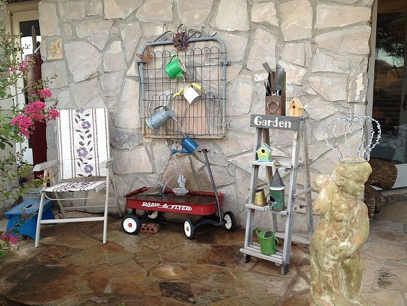 Cuter than cute! A fountain made from watering cans, a wagon & an old garden gate.