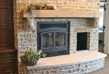 Beautiful wood burning fireplace featuring glass fireplace doors, and a majestic stone surround.