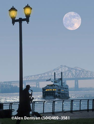 New Orleans. full moon, the Mississippi River, and a lone saxophone player under a streetlight.