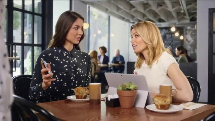 """A woman is sitting in a cafe showing pictures of her new residence to Realtor.com spokeswoman Elizabeth Banks when the two are approached by an alternate version of the home owner, dressed in inverted colors and enviously glaring at the purchased property. This """"not-you"""" wasn't able to buy the house in time, and when her demands for it are rebuked, she instead grabs the woman's muffin and stuffs it into her mouth. Though initially dazed, the two women quickly go back to the photos."""