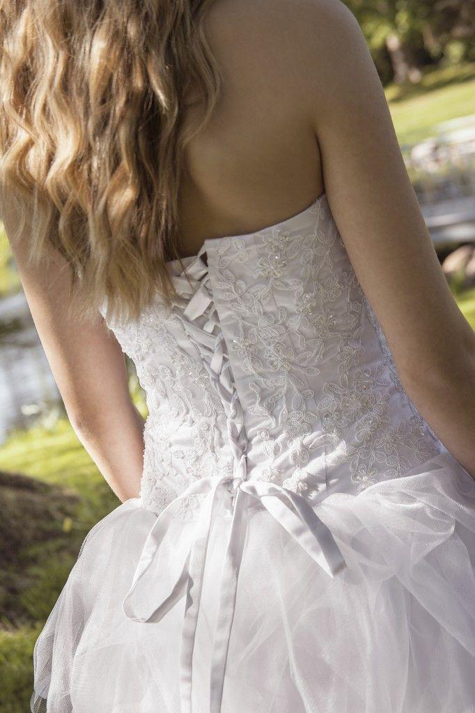 Luxux Konfirmation 2014 Confi 41 Set bagfra: Kjole med corsagetop besat med blonder og små perler. Skørtet består af flere lag tyll. Der er snøre i ryggen og den er god til den høje pige.