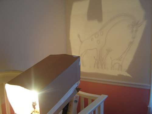 How to easily paint a mural for a nursery, bedroom, or playroom: 1) Trace the illustration to a transparency. 2) Use a clear, not frosted lightbulb and a cardboard box rolled into a square tube. Tape the transparency over one end and put the light into the other. Adjust the position of the tube to get the size you want. 3) Trace onto wall. 4) Paint inside your traced lines like a coloring book.